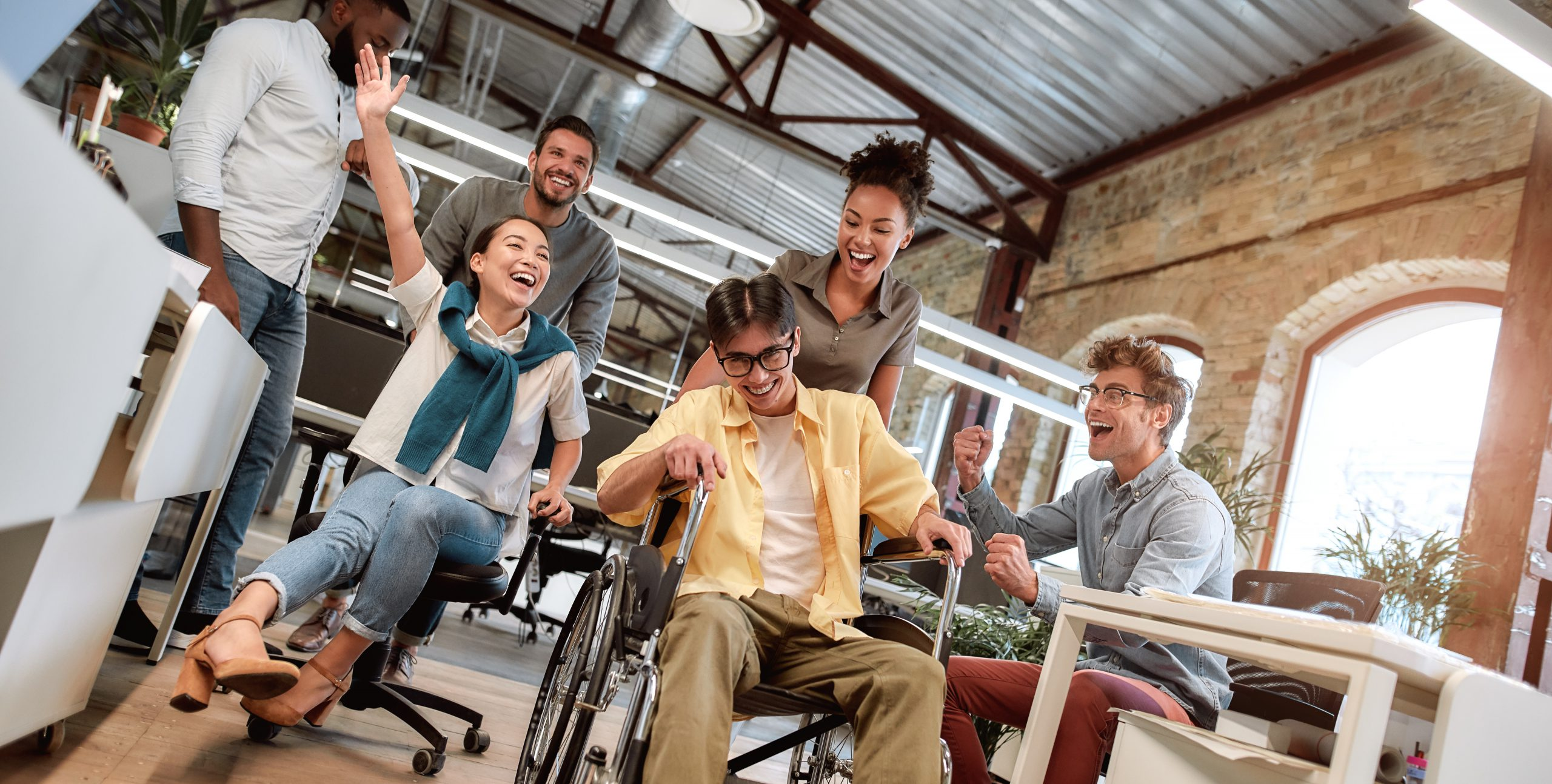 Does work make you happy. Young positive asian man in wheelchair having fun with his colleagues at modern office. Disability concept. Office fun